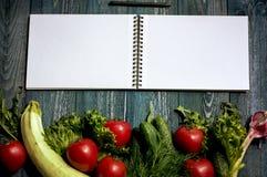 Grönsaker och notepad på träskrivbordet Arkivbilder