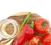 Grönsaker och olja på skärbräda, på vit Arkivbilder