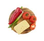 Grönsaker och ost på skärbrädan som isoleras på vit Arkivbild