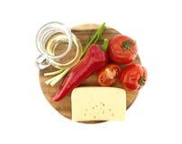 Grönsaker, olja och ost på skärbrädan som isoleras på vit Fotografering för Bildbyråer