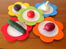 Grönsaker på de färgrika plattorna Arkivfoto