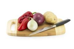 Grönsaker på ett kökbräde med kniven Royaltyfria Foton