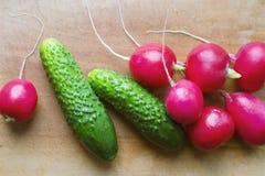 Grönsaker på träcutboard, gurkor, rädisor Arkivfoto