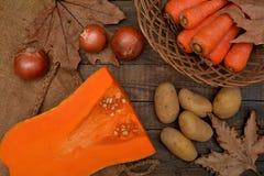 Grönsaker: pumpa, morötter, lökar och potatisar på en trätabell Arkivfoton