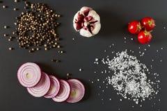Grönsaker saltar och pepprar över en mörk bakgrund royaltyfria bilder