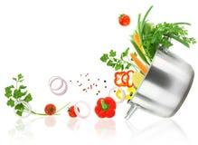 Grönsaker som är kommande ut från en rostfritt stålcasserolekruka Arkivbild