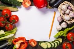 Grönsaker som beläggas med tegel runt om ett ark av papper Arkivbild