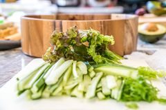 Grönsaker som framme huggas av och skivas på skärbrädan som är klar för ett strikt vegetariansushimål av en träbunke royaltyfria foton