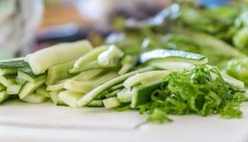 Grönsaker som huggas av och skivas på skärbrädan som är klar för ett strikt vegetariansushimål arkivfoton