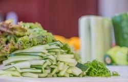 Grönsaker som huggas av och skivas på skärbrädan som är klar för ett strikt vegetariansushimål arkivbild
