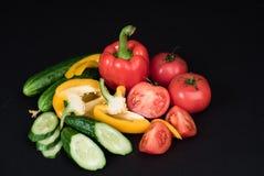 Grönsaker som isoleras på en svart bakgrund Arkivfoto