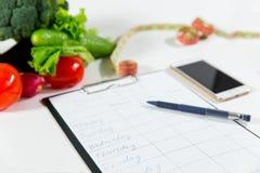 Grönsaker som mäter bandet, mobiltelefonen, bantar plan Royaltyfria Bilder