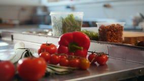 Grönsaker tomater, paprika, purjolökar som ligger på tabellen i det kommersiella köket arkivfilmer