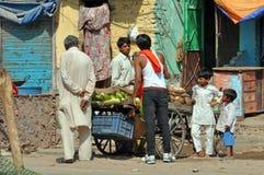 Grönsakförsäljare som köpslår med kunder i gator av Dehli, Arkivbild