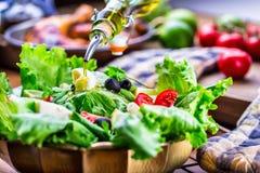 Grönsakgrönsallatsallad Olivolja som häller in i bunken av sallad Italiensk medelhavs- eller grekisk kokkonst Vegetarisk strikt v fotografering för bildbyråer