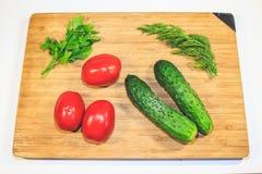 Grönsakgurkatomater på ett träbräde royaltyfri fotografi