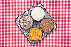 Grönsakmat En dekorativ platta med fyra bunkar med bovete, nudlar, ris och quinoaen på en röd rutig bordduk Sunt royaltyfri bild