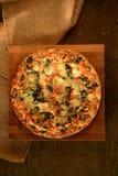Grönsakpizza med spenat- och mozzarellaost på en träbakgrund arkivfoton