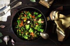 Grönsakragu i en stekpanna på en mörk trätabell arkivbild