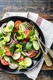 Grönsaksallad av den ny tomaten, gurkan, spenat, löken och grönsallat på plattan fotografering för bildbyråer