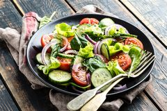 Grönsaksallad av den ny tomaten, gurkan, spenat, löken och grönsallat på plattan arkivfoton