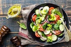 Grönsaksallad av den ny tomaten, gurkan, spenat, löken och grönsallat på plattan royaltyfri fotografi