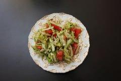 Grönsaksallad av kål och tomaten på en platta Arkivfoto