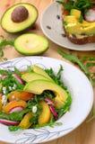 Grönsaksallad med avokadot, arugula, rädisan och persikan Diet-sund mat spelrum med lampa Top beskådar Närbild Royaltyfri Foto