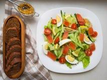 Grönsaksallad med Breadon en vit platta, med bröd på ett djupt bräde sund mat, grön frukost arkivfoto