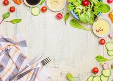 Grönsaksalladförberedelsen med dressingar, ingrediensbestick och kök kontrollerade servetten på ljus lantlig bakgrund, bästa sikt Arkivfoton