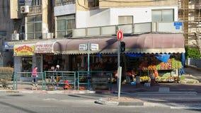 Grönsakshandlare shoppar med den urblekta röda parasollmarkisen Fotografering för Bildbyråer