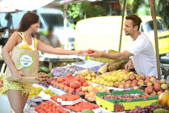 Grönsakshandlare som ut räcker en frukt till en konsument. Fotografering för Bildbyråer