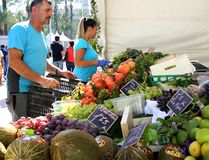 Grönsakshandlaresäljare, en man och en kvinna, förbereder deras grönsaker och fruktstall royaltyfri fotografi