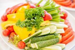 Grönsakskivor med gurkan, tomater, paprika, grönsallat, dill och örter på den vita plattan Slut upp med den selektiva fokusen Arkivbild