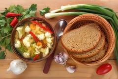 Grönsaksoppa av blomkålen, morötter, tomaten, peppar i en platta med en sked, bröd och lökar på en träbakgrund royaltyfri fotografi