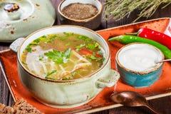 Grönsaksoppa, buljong med nudlar, örter, persilja och grönsaker i bunke med gräddfil, kryddan, peppar, torkade timjan Royaltyfri Bild