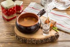Grönsaksoppa i lerakrukan som tjänas som med vodka som häller i skjutit exponeringsglas på trätabellen royaltyfria foton