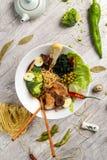 Grönsaksoppa med kött, nudlar och grönsaker i en vit platta Arkivbilder