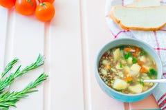Grönsaksoppa med lägenheten för den bästa sikten för linser lägger på träpastellfärgad bakgrund med körsbärsröda tomater, rosmari Royaltyfri Fotografi
