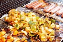 Grönsaktofu och varmkorv som grillar på galler Arkivfoton