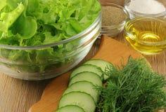 Grönsallat i en glass genomskinlig salladbunke med kryddor Arkivfoton