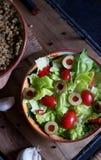 Grönsallatsallad, tomater och oliv Arkivbilder