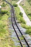 Grönska gräs järnvägspår bland berget Fotografering för Bildbyråer