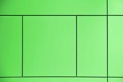 grönska Grön bakgrund som korsas av linjer som bildar fyrkanter och rektanglar i en abstrakt arkitektonisk vägg Fotografering för Bildbyråer