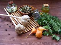 Grönska: ny persilja och dill, löken, vitlök, olivolja i exponeringsglas, torkar kryddor i bunke, och enbär är ideala för modig n Royaltyfri Bild