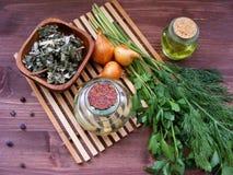 Grönska: ny persilja och dill, löken, vitlök, olivolja i exponeringsglas, torkar kryddor i bunke, och enbär är ideala för modig n Arkivbild