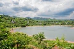 Grönskande lakeshore i molnig vår Royaltyfri Fotografi