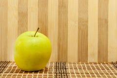Grönt äpple framme träbakgrunden Fotografering för Bildbyråer