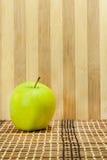 Grönt äpple framme träbakgrunden Arkivfoto