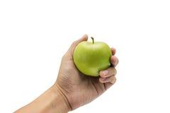 Grönt äpple i hand på isolerad bakgrund Arkivbild